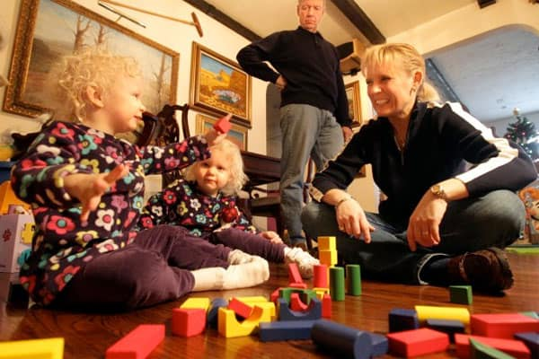 The Christian family, left to right, twins Reagan, and Darby, 2, and Fred and Linda play with building blocks in their Belleville home Monday Dec. 26, 2011. The girls were conceived through mini in vitro fertilization, a procedure advocated by St. Louis doctor Sherman Silber which, he says, is safer, cheaper and easier on women while maintaining comparable pregnancy rates.